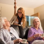 A young woman talking with two elderly ladies