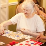 An elderly lady playing a board game