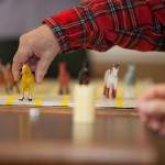 A man playing with miniature figures