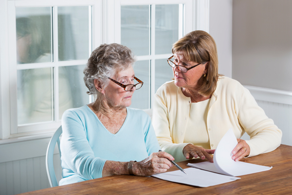 A lady explaining to a senior the benefits of moving to an independent living facility