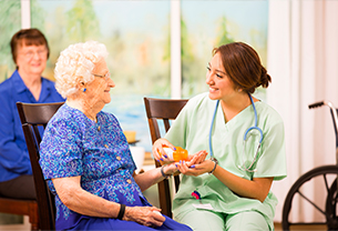 A nurse giving medicine to a senior at the Wyndemere Woods Assisted and Independent Living Facility in Woonsocket