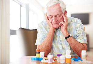 A confused old man with medicines in front of him