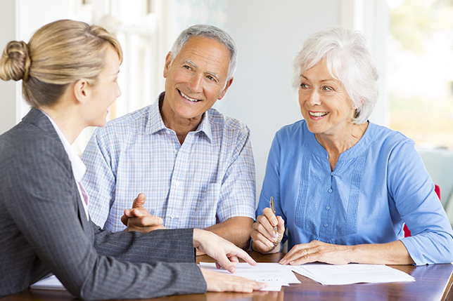 Happy Senior Couple With Financial Advisor At Home Explaining About Retirement Residence