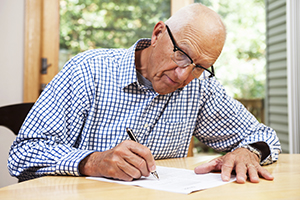 Senior man filling out paperwork and signing document for retirement residence