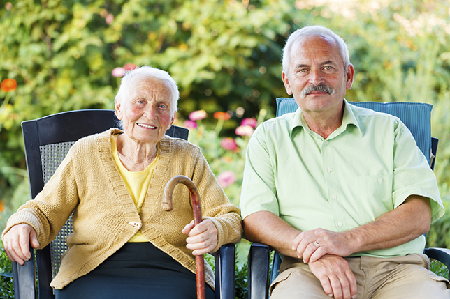 An old Lady holding a stick sitting to a senior man