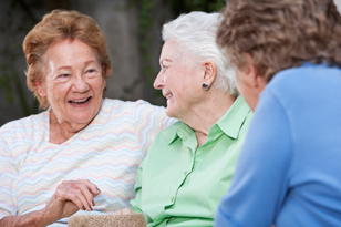 Three elderly women talking at an assisted living facility