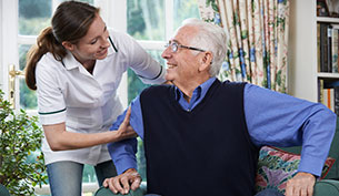 Care Worker Helping a Senior Man To Get Up
