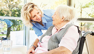 Senior woman in a wheelchair being attended by an assisted living facility female staff