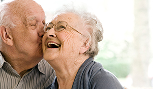 Elderly Man kissing his wife on a Couch in an assisted living facility