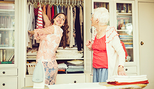 A young lady cleaning the wardrobe while a senior woman watches