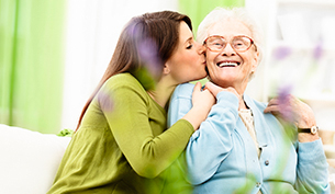 A lady kissing her old grand mother