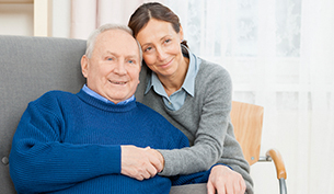Senior Man In Wing Chair with Caregiver