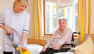 Senior Woman Instructing a Young Nurse While Cleaning in a Care Home