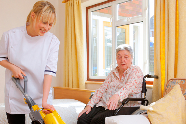 young Nurse cleaning for senior woman in a care home