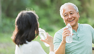 Senior Asian Couple Drinking Water After an Outdoor Walk
