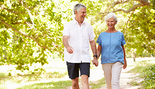 Senior Couple Walking on a Path and Smiling