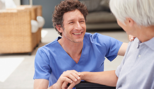 Friendly Male Nurse Assisting a Senior Patient with Walking at an Assisted Living Facility