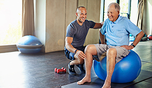 A Fitness Trainer Helping and Elderly Balance on a Gym Ball