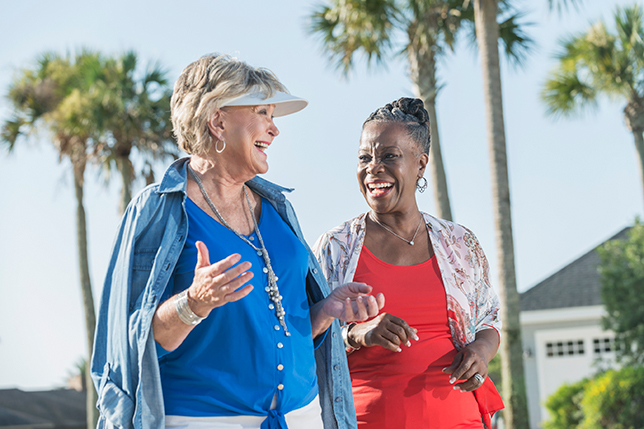 Two senior women walking and talking outdoors