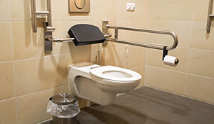 A high level toilet with a handrail for disabled and/or senior people