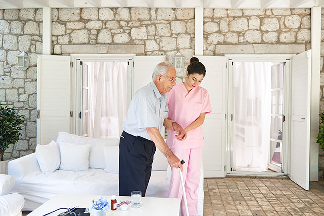 Female nurse helping elderly man