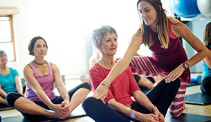 Yoga Instructor Helping a Senior Lady in Class