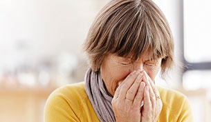 Senior Woman Blowing Her Nose Due To An Allergic Reaction