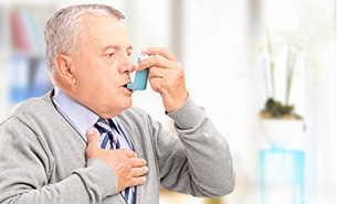 Senior Male Treating Asthma With Inhaler