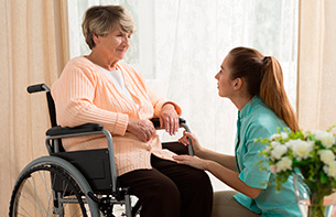 Caregiver Helping Old Female at an Assisted Living Facility