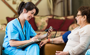 Nurse Checks Senior Patient's Blood Pressure at an Assisted Living Facility