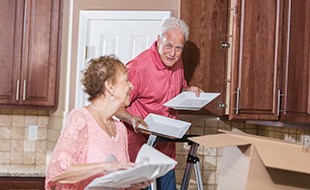 Senior Couple Moving House Packing Kitchen Stuff