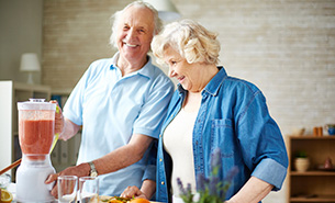 Senior Couple in Kitchen Making Fresh Fruit Juice