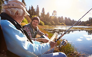 Father and Adult Son Fishing Lakeside While Taking Time Off from Senior Living Community