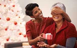A Caregiver at Retirement Residence Giving a Gift to a Senior Resident Lady