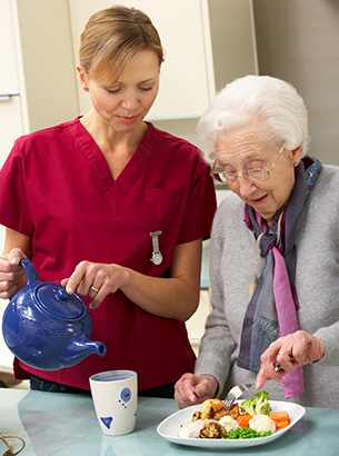 Senior woman with carer eating meal at an assisted living facility