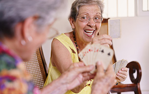 Old Women Enjoy Playing Card Game at an independent living facility
