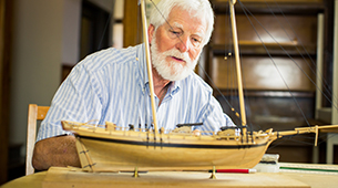 A Senior Man Working On a Model Boat